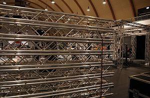 Aufbauhelfer und Stagehands bauen Traversen und Absperrgitter auf.
