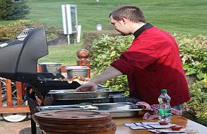 Koch beim Sommerfest auf Golfplatz bereitet das Barbeque vor. Mietköche von all about event.