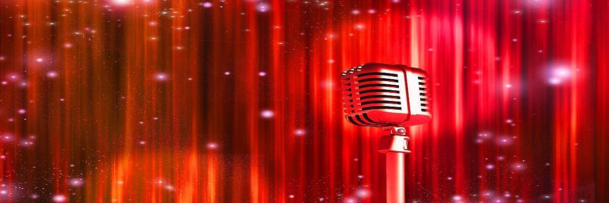 Silbernes Mikrofon vor rotem Vorhang. Dialoge fördern. Moderatoren von all about event.