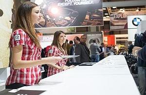 Messehostessen in kariertem Hemd im Gespräch mit Kunden